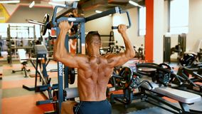 L'athlète bel s'exerce au centre de gymnase La formation dure d'homme de Bodybuilder muscles à la machine de formation banque de vidéos