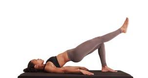 L'athlète d'isolement de femme de métis faisant la hanche augmente sur mat photographie stock