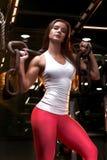 L'athlète de jeune femme est se reposant et posant après les exercices avec la chaîne images libres de droits