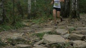 L'athlète de jeune fille courant dans la forêt sur des roches traînent clips vidéos