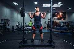 L'athlète dispose à faire des postures accroupies avec le barbell photo stock