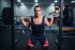L'athlète dispose à faire des postures accroupies avec le barbell image libre de droits