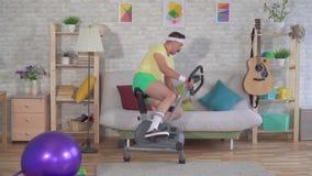 L'athlète drôle d'homme des années 80 avec une moustache tombe le vélo d'exercice sur le divan MOIS lent banque de vidéos