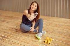 L'athlète féminin fait une pause avec de l'eau potable après une séance d'entraînement qu'un athlète dans les vêtements de sport  photo stock