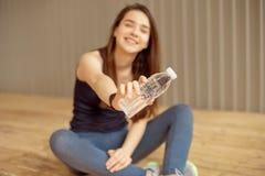 L'athlète féminin fait une pause avec de l'eau potable après une séance d'entraînement qu'un athlète dans les vêtements de sport  photos libres de droits