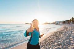 L'athlète féminin réussi faisant les pouces positifs lèvent le geste et les écouteurs de port avant le fonctionnement ou l'exerci images stock