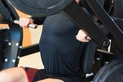L'athlète fait des exercices de presse de coffre sur la vue étroite de machine de gymnase photos stock
