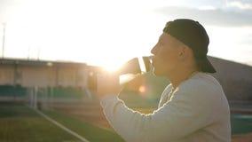 L'athlète fatigué avec le chapeau de naseball boit l'eau de la bouteille sur la voie de stade banque de vidéos