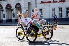 L'athlète masculin avec une incapacité sur un fauteuil roulant monte par des rues de ville photographie stock libre de droits