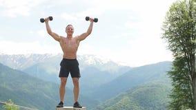 L'athlète masculin musculaire avec des bras a soulevé faire les haltères de levage d'exercices banque de vidéos