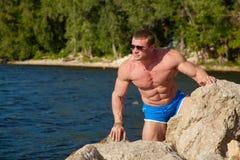 L'athlète mince avec de grands muscles posent à l'appareil-photo Photographie stock libre de droits