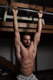 L'athlète Performing Hanging Leg soulève des exercices de l'exercice ab Image stock