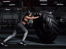 L'athlète pousse une grande roue Exercice avec le poids lourd dans le gymnase Photographie stock