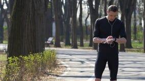 L'athlète professionnel avec le smartphone et les mains libèrent vérifier des traqueurs de forme physique banque de vidéos