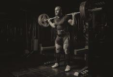 L'athlète professionnel fait des postures accroupies avec une barre Images libres de droits