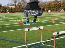L'athlète sautant par-dessus un obstacle pour la force et l'agilité pratiquent photo stock