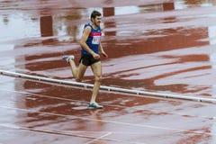 L'athlet d'homme courent 400 mètres sous la pluie Photos libres de droits