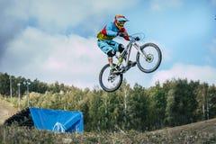 L'athlète sur un vélo de montagne vole dans un saut d'un tremplin Images stock