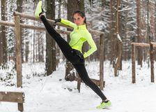 L'atleta adatto della donna che fa l'allungamento spaccato della gamba sinistra si esercita all'aperto in legno Esercitazione di  Fotografia Stock