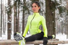 L'atleta adatto della donna che fa l'allungamento spaccato della gamba sinistra si esercita all'aperto in legno Esercitazione di  Fotografie Stock Libere da Diritti
