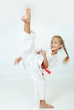 L'atleta allegro in un kimono esegue un'alta circolare della gamba di scossa Fotografie Stock