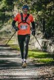 L'atleta anziano funziona con i bastoni alla distanza della passeggiata della corsa Fotografie Stock Libere da Diritti