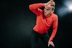 L'atleta attraente dell'uomo che si rilassa dopo l'allenamento duro alla palestra, ha messo la sua mano sulla testa Uomo sportivo Fotografie Stock