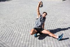 L'atleta bello che esercita il turco si alza fotografia stock