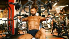 L'atleta bello sta esercitandosi nel centro della palestra L'addestramento duro dell'uomo del culturista muscles alla macchina di stock footage