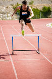 L'atleta che salta sopra la transenna Fotografia Stock