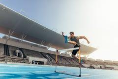 L'atleta che salta sopra una transenna sulla pista corrente Immagini Stock