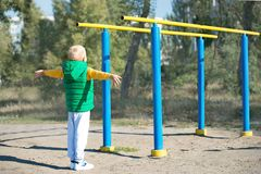 L'atleta del ragazzo che fa la tirata aumenta Stile di vita attivo Il bambino si esercita sulle barre irregolari sulla via fotografie stock