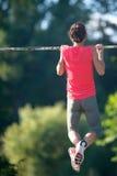 L'atleta della donna di sport è Chin-UPS e Pullups che si prepara su un aband Immagine Stock Libera da Diritti