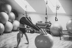 L'atleta della donna fa il verticale con le gambe sulla palla di misura Fotografia Stock Libera da Diritti
