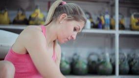 L'atleta della giovane donna sta preparando per la formazione con il kettlebell La ragazza sfrega il kettlebell con magnesia per  stock footage