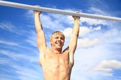 L'atleta della gioventù sulla trave trasversale Fotografie Stock