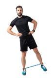 L'atleta di forma fisica che fa gli gamba-ascensori laterali si esercita con le bande della resistenza Fotografia Stock