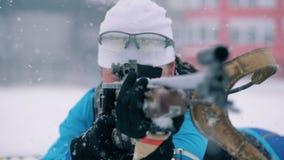 L'atleta di signora è trovantesi e preparante sparare in mezzo a pratica di biathlon stock footage