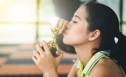 L'atleta femminile asiatico sta baciando il suo trofeo con orgoglio nel successo immagini stock