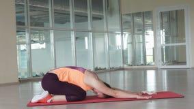 L'atleta femminile sveglio fa l'esercizio d'allungamento difficile sulla stuoia della palestra mentre si prepara nella palestra Immagine Stock Libera da Diritti