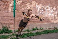 L'atleta maschio è un allenamento eccellente integrale, estorto fuori in natura in città di estate, addestramento del trx, ritien Fotografia Stock