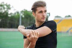 L'atleta maschio concentrato fa l'allungamento degli esercizi all'aperto Immagini Stock