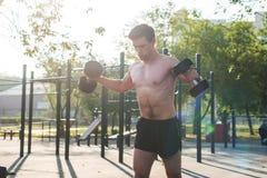 L'atleta maschio muscolare con le armi ha sollevato fare le teste di legno di sollevamento di esercizi immagini stock libere da diritti
