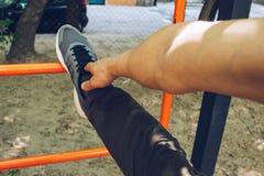 L'atleta maschio nell'eseguire la condizione delle scarpe di sport allunga la sua gamba sul campo sportivo con una scala del meta fotografia stock