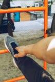 L'atleta maschio nell'eseguire la condizione delle scarpe di sport allunga la sua gamba sul campo sportivo con una scala del meta fotografia stock libera da diritti