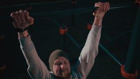 L'atleta maschio sta preparandosi sulla barra orizzontale nella notte nell'iarda della città video d archivio