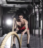 L'atleta muscolare con la battaglia della corda di battaglia ropes l'esercizio nella f Fotografia Stock