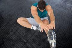 L'atleta sta allungando sul pavimento nero Immagine Stock