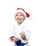 L'atleta in un kimono ed in un beanie di Santa Claus tiene le mani su difesa Fotografie Stock Libere da Diritti