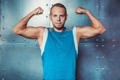 L'atleta, uomo muscolare dello sportivo mostra i suoi muscoli e l'esame della macchina fotografica Immagini Stock